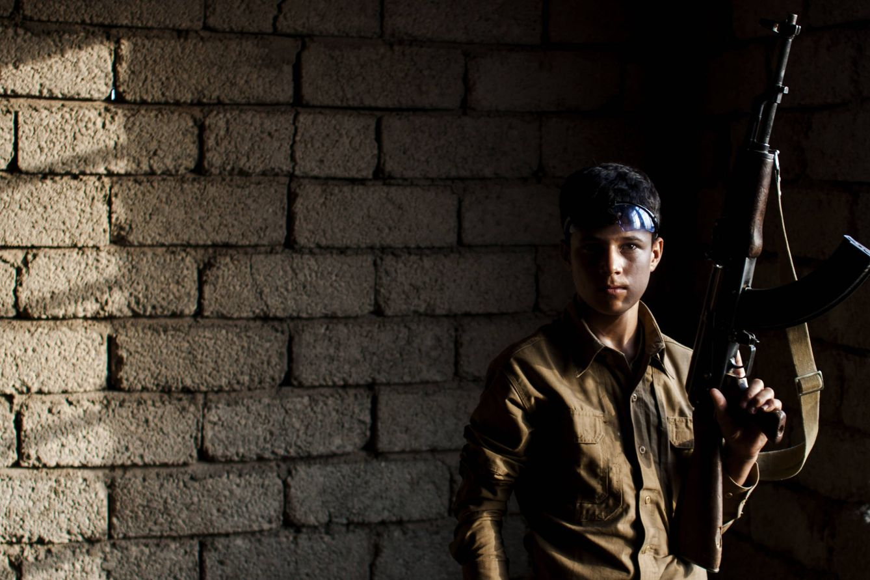Foto: Ali Husein, 15 años, el combatiente más joven de la milicia del Jeque Nazar, posa con su kalashnikov (Foto: Ethel Bonet).