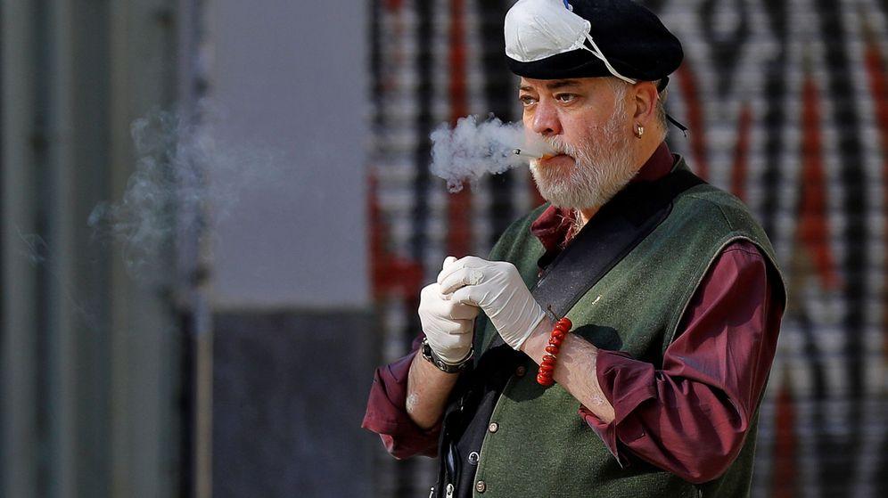 Foto: Un hombre se retira por un momento su mascarilla de protección para fumar un cigarrillo. (EFE)