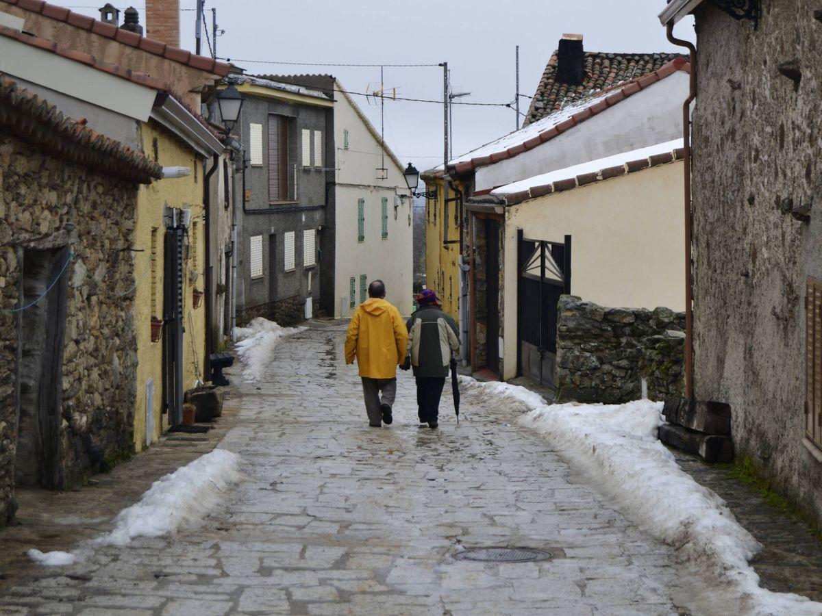 Foto: Dos personas, paseando por el pueblo madrileño de La Acebeda. (M. Z.)