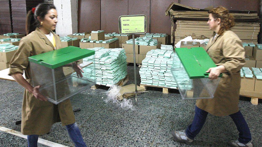 Foto: Dos trabajadoras del Ayuntamiento de Sevilla transportan urnas electorales. (EFE/Eduardo Abad)