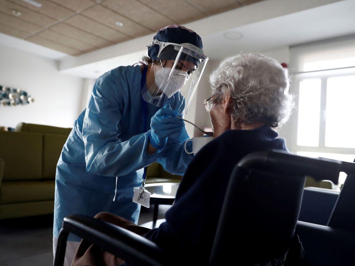 Foto: Una cuidadora ayuda a comer a una anciana en la residencia Casablanca, en el barrio madrileño de Villaverde. (EFE)