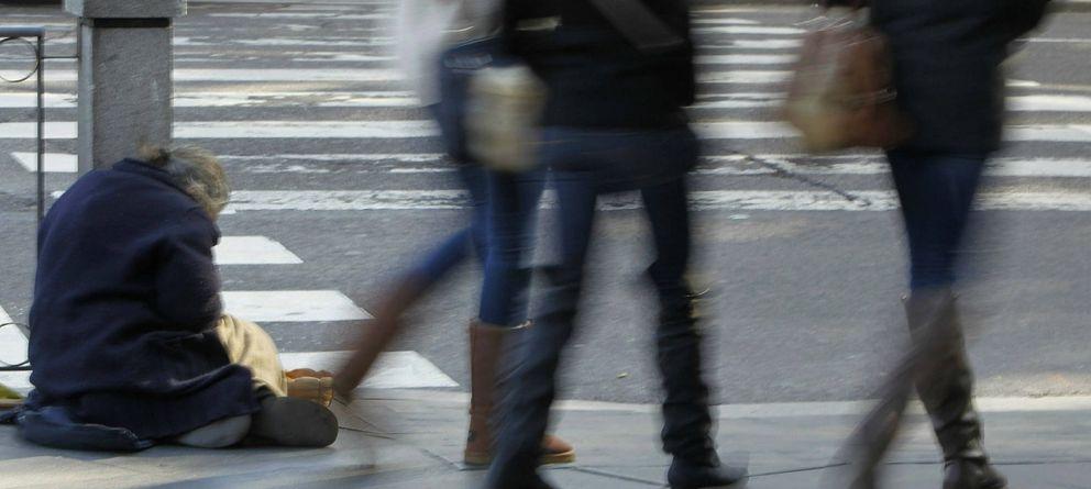 Foto: Un mendigo pide limosna ante la indiferencia de los transeuntes en la Plaza de Cibeles. (EFE)