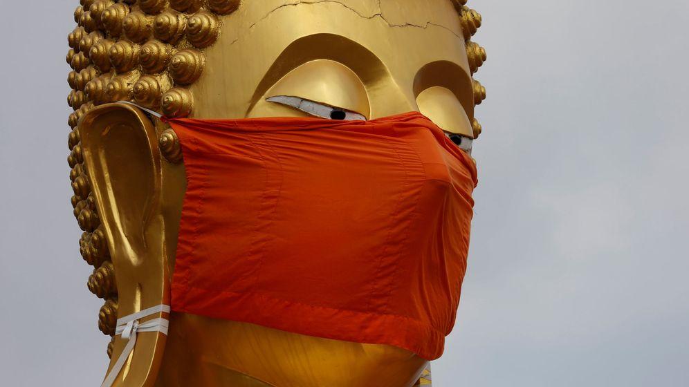 Foto: Una estatua de Buda con mascarilla en Tailandia. (Reuters)