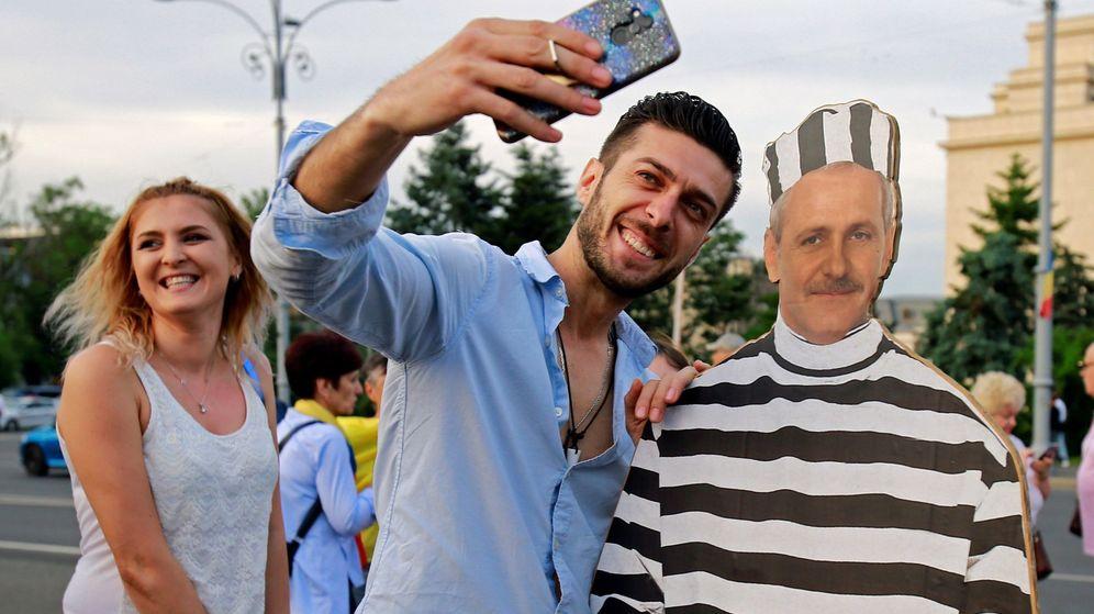 Foto: Dos personas haciéndose un selfi con una imagen de cartón de Liviu Dragnea vestido de preso. (EFE)