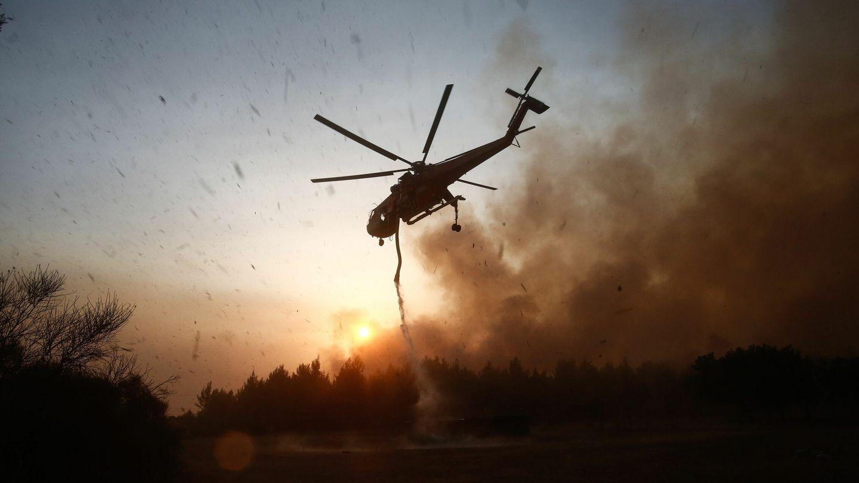 Un helicóptero trabaja para apagar el incendio en Varybobi. (EFE)