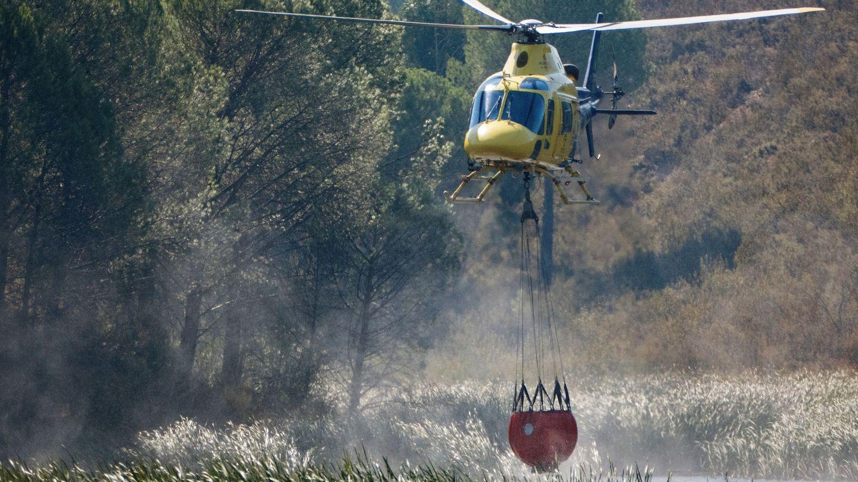 Un helicoptero carga agua para sofocar el avance de las llamas y el fuerte viento en el incendio forestal de Almonaster la Real, en Huelva. (EFE)
