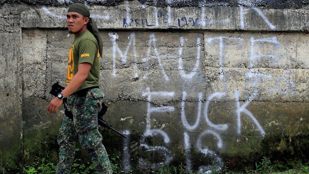 Foto: Un soldado filipino pasa frente a un antiguo grafitti de apoyo a los yihadistas, modificado por un desconocido, en Marawi, el 2 de junio de 2017. (Reuters)