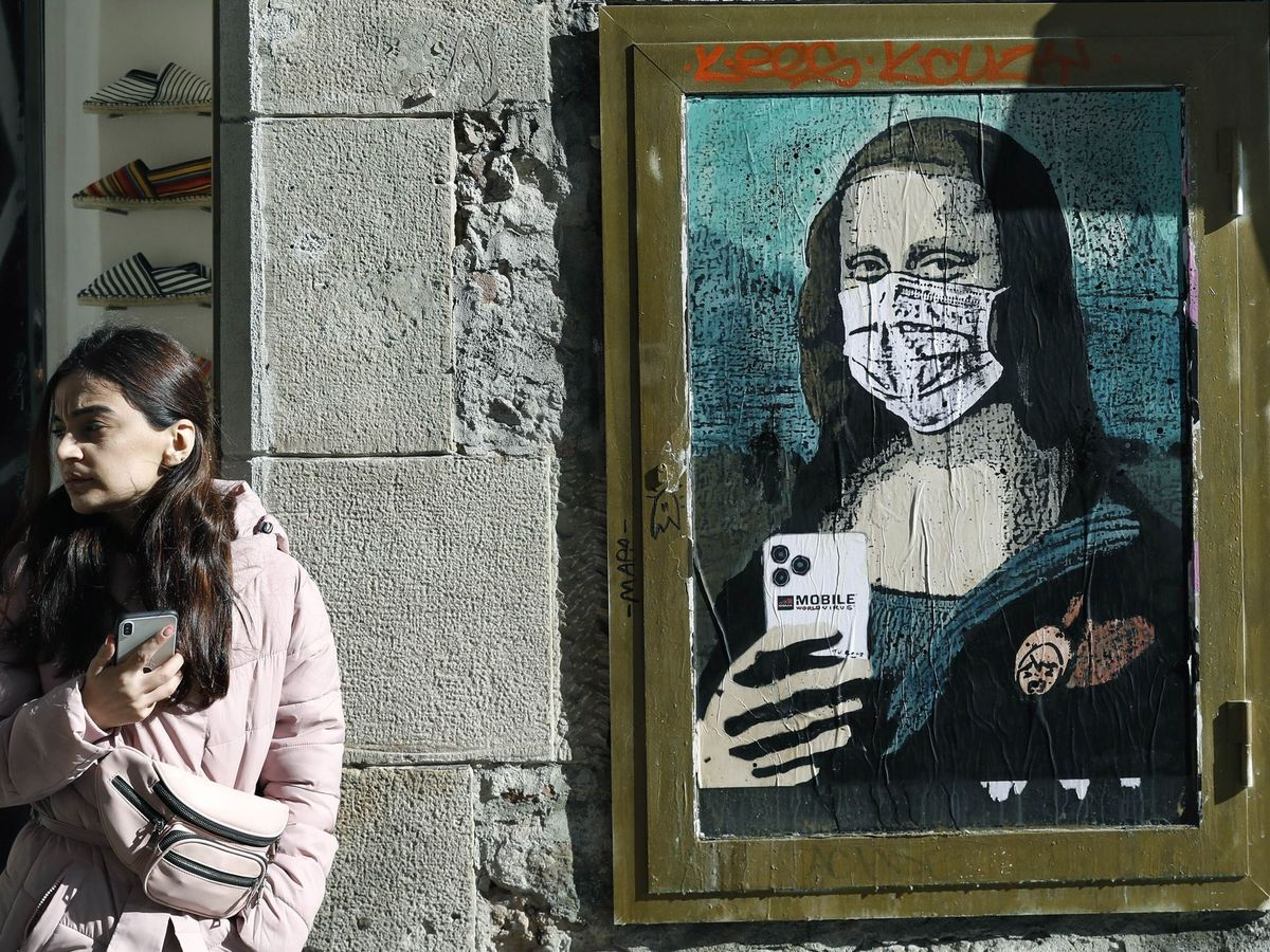 Foto: Una Gioconda con mascarilla y móvil en una calle de Barcelon. (EFE)
