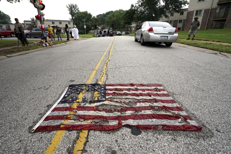 Foto: Una bandera de EEUU parcialmente quemada en la calle donde murió Michael Brown, en Ferguson, el 9 de agosto de 2015 (Reuters).
