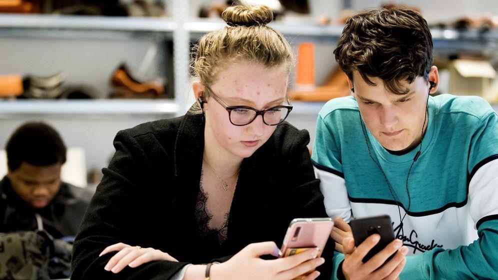 Foto: Dos jóvenes utilizan sus teléfonos móviles. (EFE)