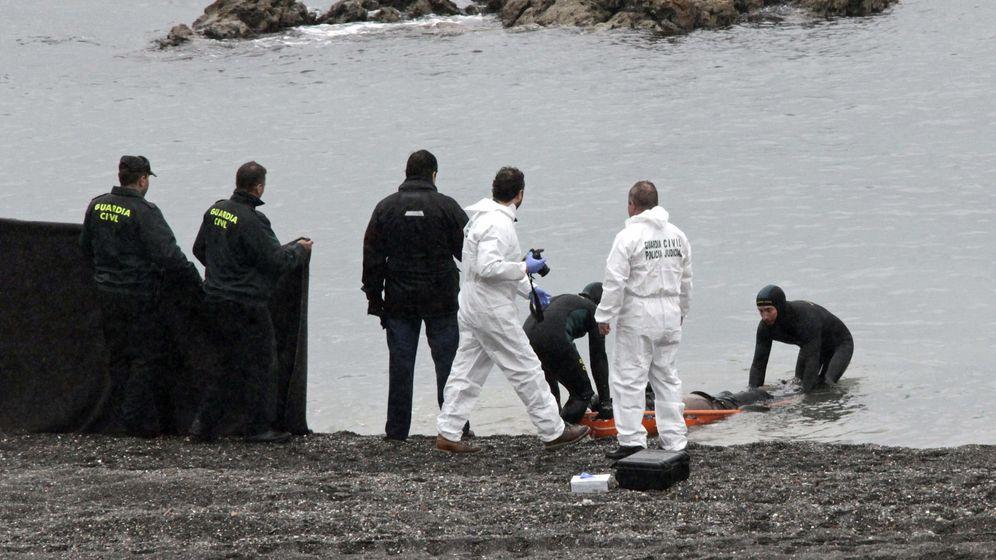 Foto: Varios guardias civiles recogiendo el cadáver de uno de los subsaharianos que murieron en El Tarajal. (EFE)