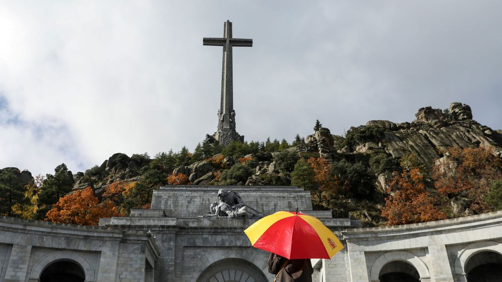 Foto: Una mujer sujeta un paraguas con los colores de la bandera de España en el Valle de los Caídos. (Reuters)
