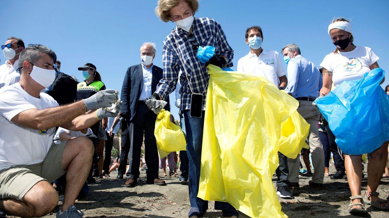 La reina Sofía en Málaga, colaborando en tareas de recogida de residuos en la playa. (EFE)