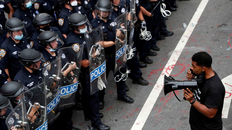 Un manifestante frente a agentes antidisturbios de la policía de Nueva York. (Reuters)