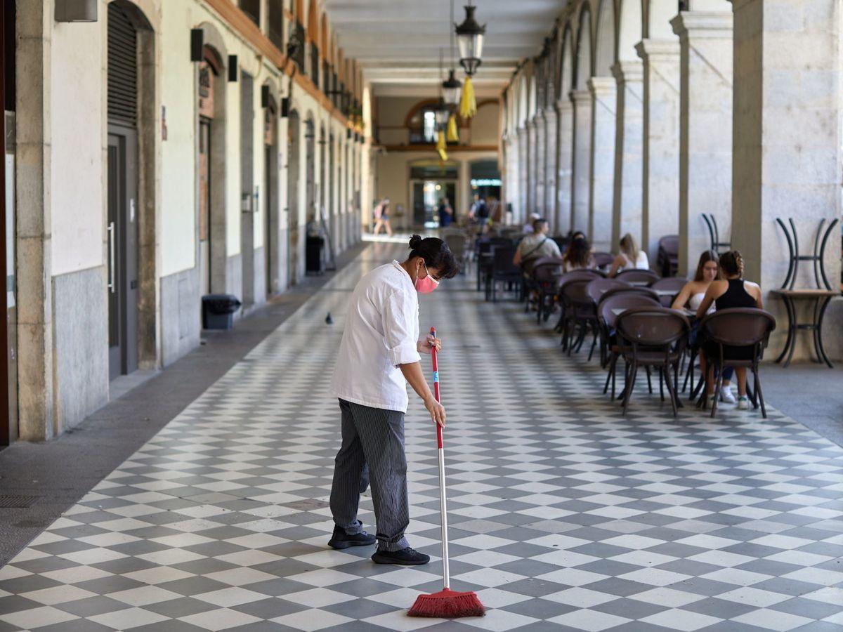 Foto: Una trabajadora realiza tareas de limpieza en una plaza de Girona. (EFE)