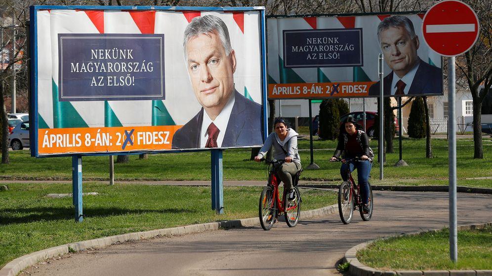 Foto: Dos ciclistas pasan delante de varios pósteres electorales del presidente Víktor Orbán, en Gyongyos, Hungría, el 8 de abril de 2018. (Reuters)