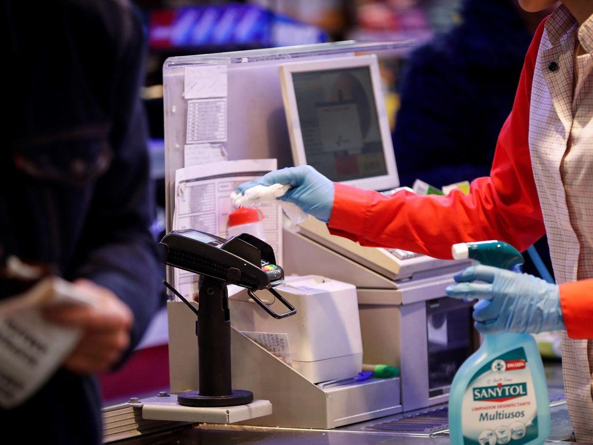 Foto: Cajera desinfectando un datáfono. (EFE)