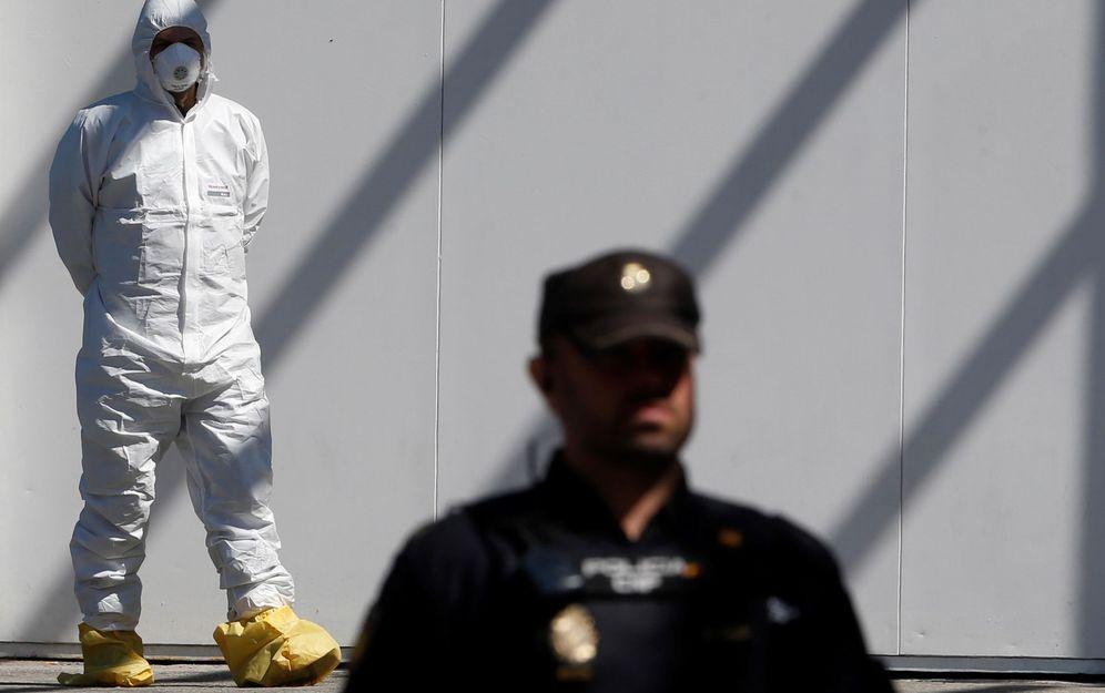 Foto: Policías nacionales montan guardia mientras trabajadores del servicio funerario realizan sus labores en el Palacio de Hielo de Madrid. (EFE)