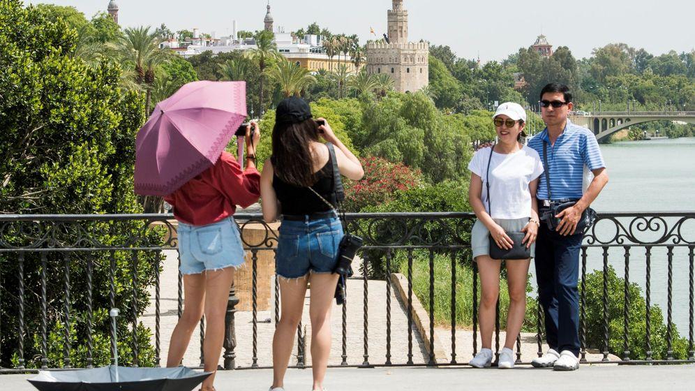 Foto: Turistas se protegen del sol en el centro de Sevilla. (EFE)