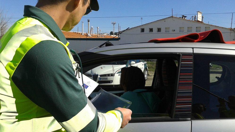 Foto: Agente de la DGT revisando la documentación de un conductor y de su vehículo.