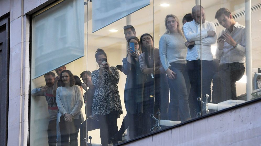 Foto: Un grupo de oficinistas observa la escena del crimen. (EFE)