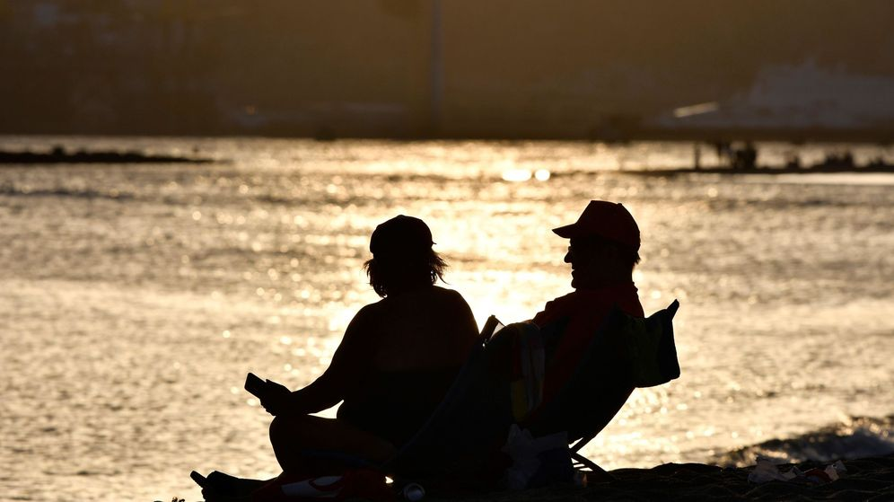 Foto: Dos personas descansan en una playa de Almería en una Noche de San Juan sin hogueras (EFE)