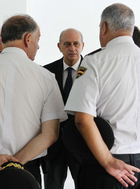 Foto: El ministro del Interior, Jorge Fernández Díaz, entre dos policías (EFE)