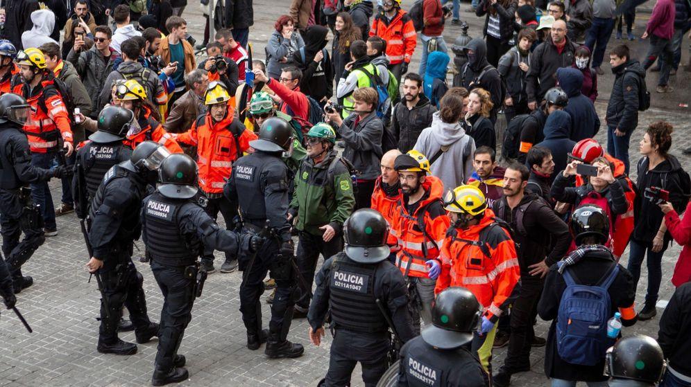Foto: Bomberos montan un cordón entre 'mossos' y manifestantes para evitar incidentes. (EFE)