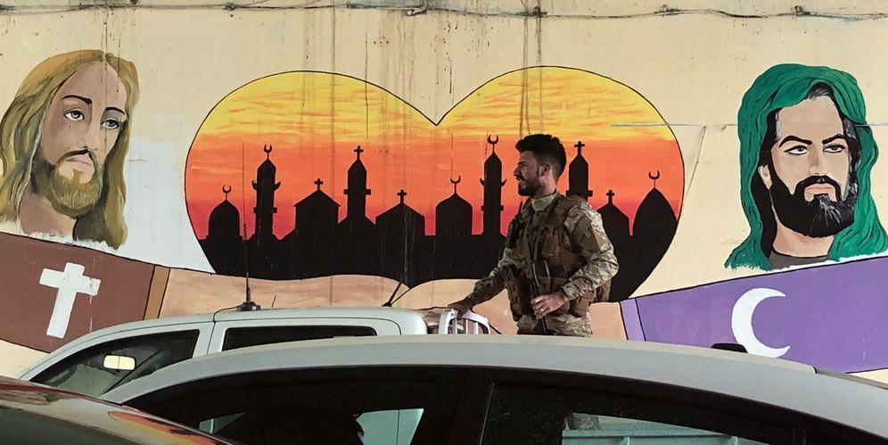 Foto: Un miembro de las Unidades de Movilización Popular en la parte trasera de una camioneta frente a un mural a favor de la tolerancia religiosa en Bagdad, el 8 de mayo de 2018. (Reuters)