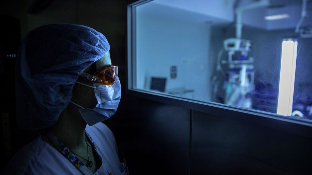 Foto: Un sanitario asomándose por una ventanilla. (EFE)
