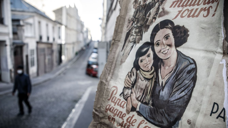 Foto: Un cartel de propaganda de la II Guerra Mundial decía 'No más días malos, papá gana dinero en Alemania' en una calle desierta transformada en un plató de cine en París que se interrumpió por el coronavirus (EFE)