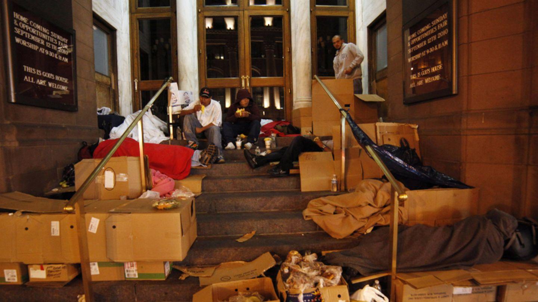 Vagabundos comen alimentos donados por una asociación caritativa en una calle de Nueva York (Reuters).