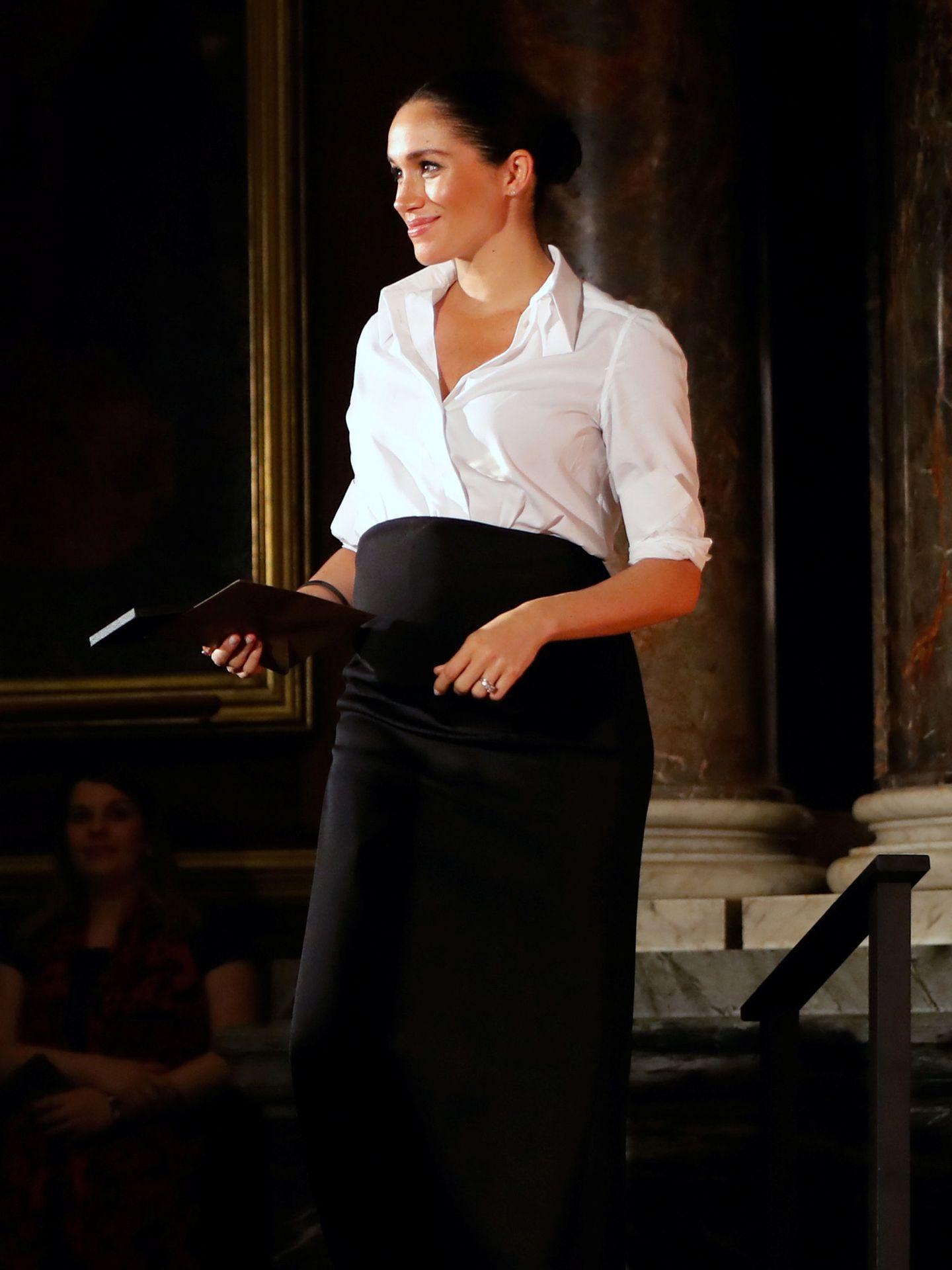 Meghan Markle con look de camisa blanca y falda negra en una gala de premios. (Reuters)