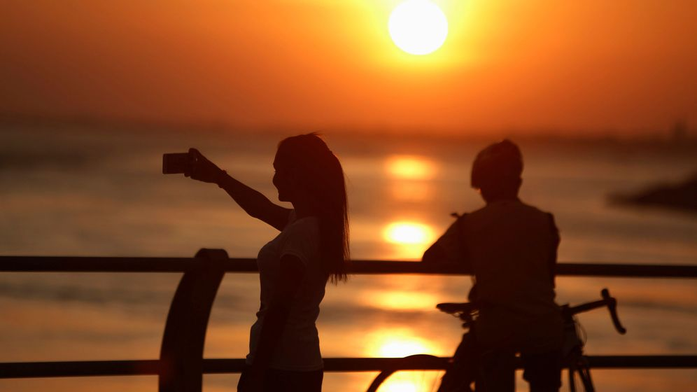 Foto: Mujeres se hacen selfies al borde del mar. (Reuters)