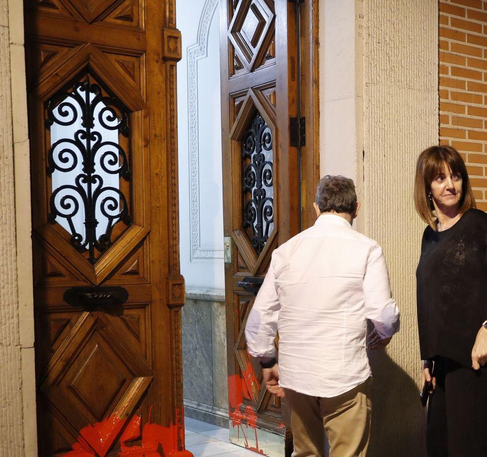Foto: Idoia Mendia y Alfonso Gil observan los daños en el portal de su vivienda tras el ataque. (EFE)