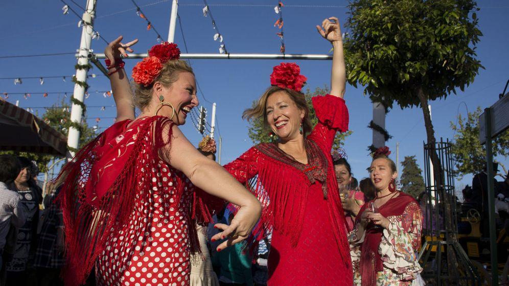 Foto: Mujeres ataviadas con trajes de gitana bailan en las casetas del Real. (EFE)