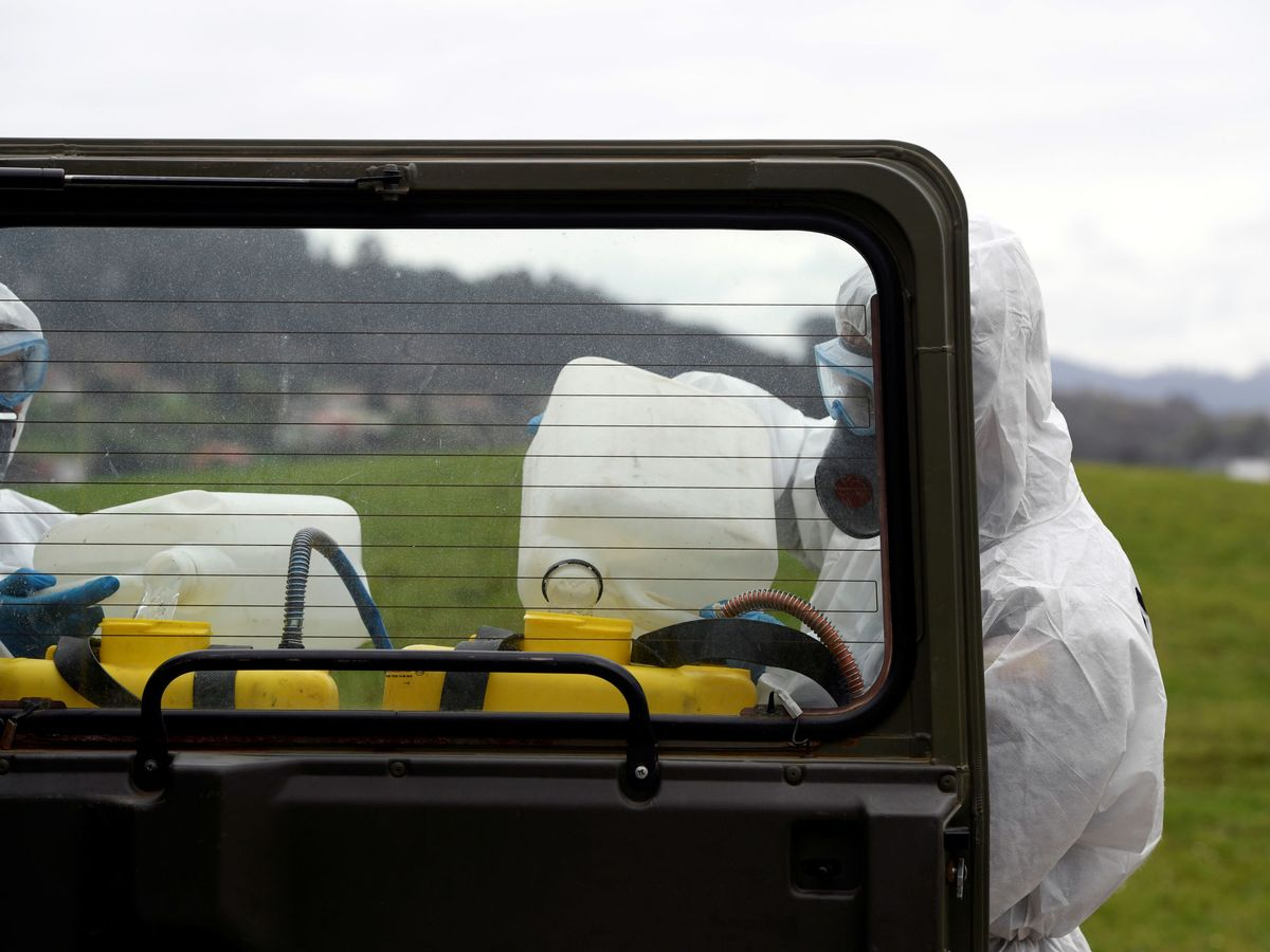 Foto: Miembros de la UME desinfectan el área que rodea al Hospital Universitario Central de Asturias en Oviedo. (EFE)