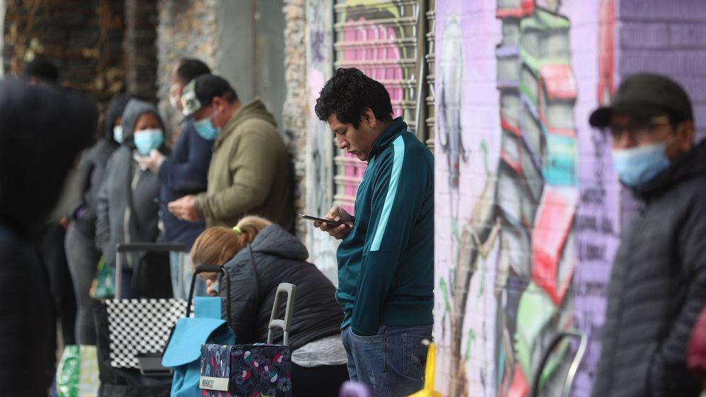 Foto: Vecinos de Aluche, Madrid, hacen cola para recoger alimentos (EFE)