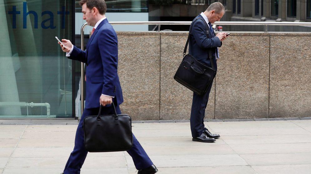 Foto: Trabajadores comprueban sus teléfonos móviles en plena calle. (Reuters)