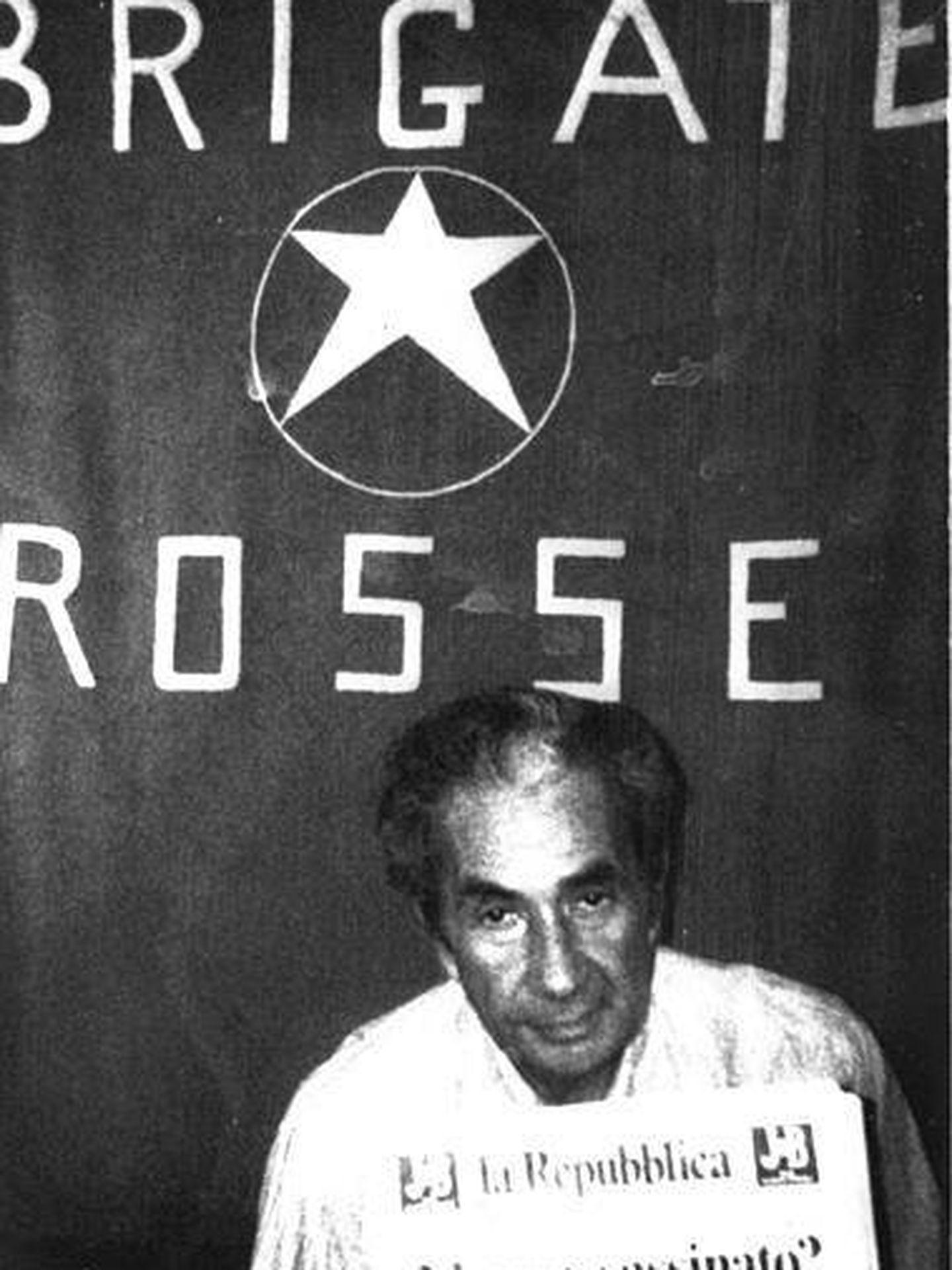Aldo Moro en el lugar del secuestro junto a la bandera de las Brigadas Rojas.