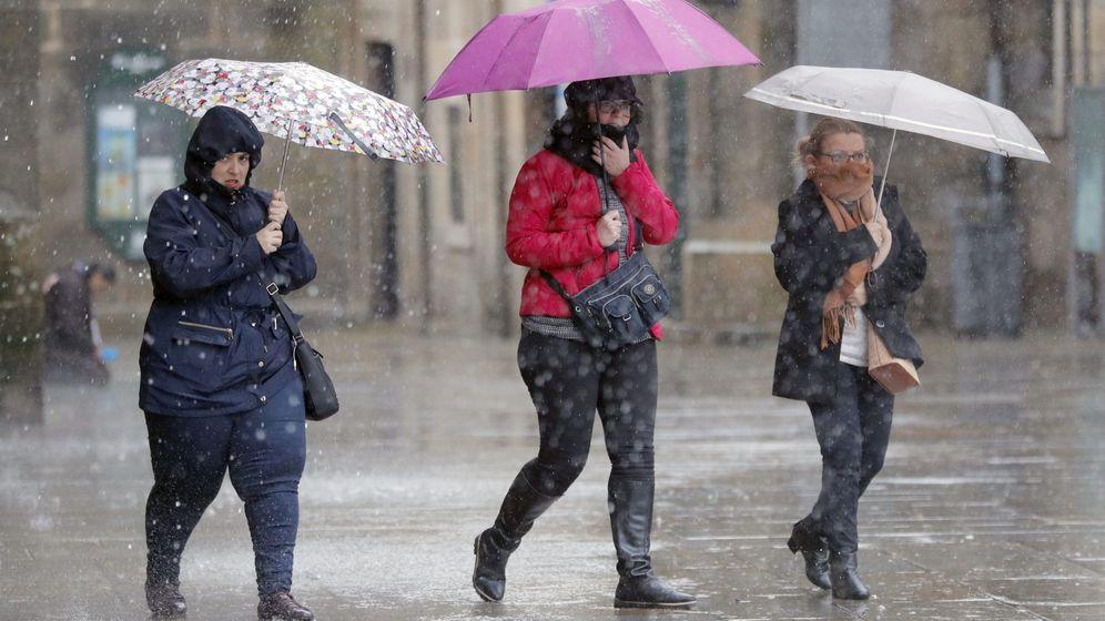 Foto: Varias personas transitan bajo la lluvia la plaza del Obradoiro, en Santiago de Compostela. (EFE)