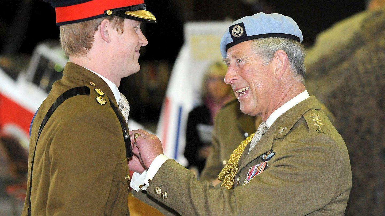 El príncipe Harry recibiendo de manos de su padre las 'alas' que le acreditan como piloto de helicóptero. (EFE)