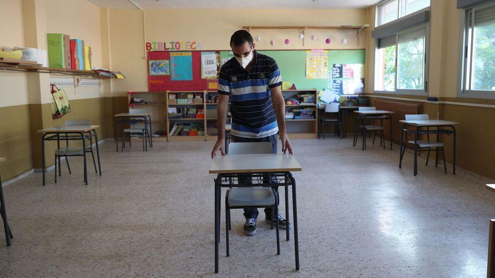 Foto: Un profesor separa la mesas de su aula, para favorecer la distancia social, en un colegio madrileño. (EFE)