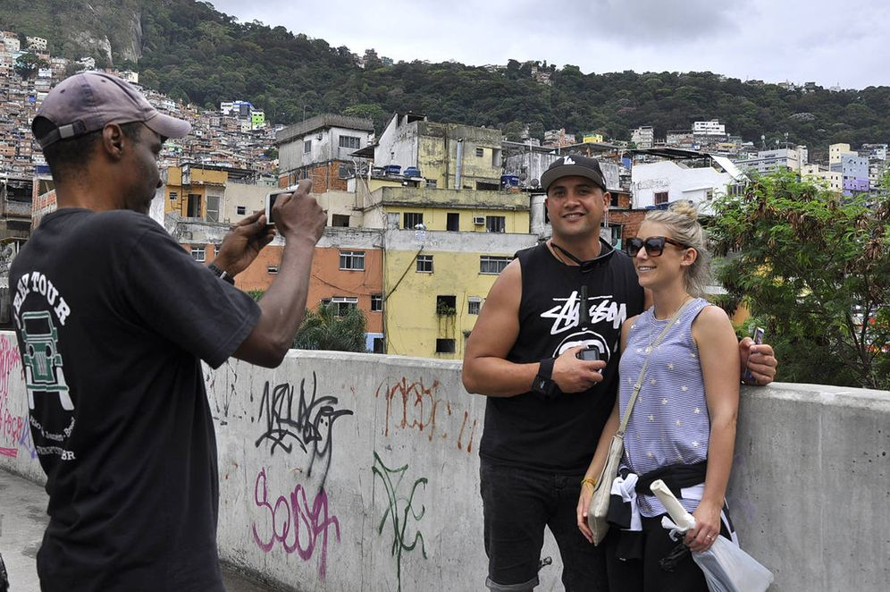 Foto: Dos turistas se fotografían en la favela Rocinha, la mayor de Brasil, donde se organizan 'tours' para extranjeros. (V. Saccone)