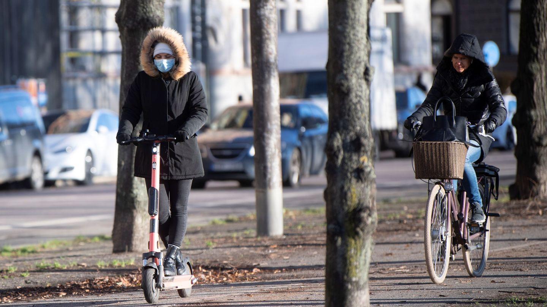Mujer con patinete y mascarilla en Estocolmo. (Reuters)