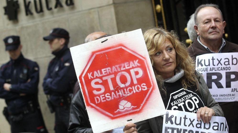 Foto: Miembros de Kaleratzeak Stop Desahucios e IRPH-STOP participan en una concentración frente a la sede de Kutxabank en San Sebastián. (EFE)