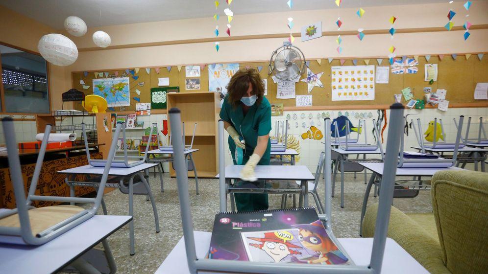 Foto: Una limpiadora desinfecta el mobiliario del colegio Cervantes de Córdoba. (EFE)