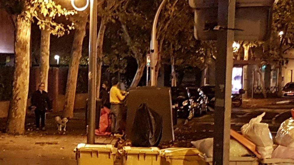 Foto: Dos personas, robando en Madrid papel y cartón de un contenedor.
