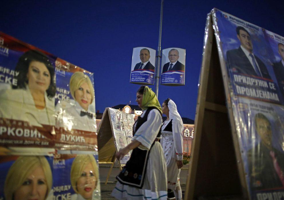 Foto: Serbias pasan ante carteles electorales en Bijeljina días antes de la jornada electoral (Reuters).