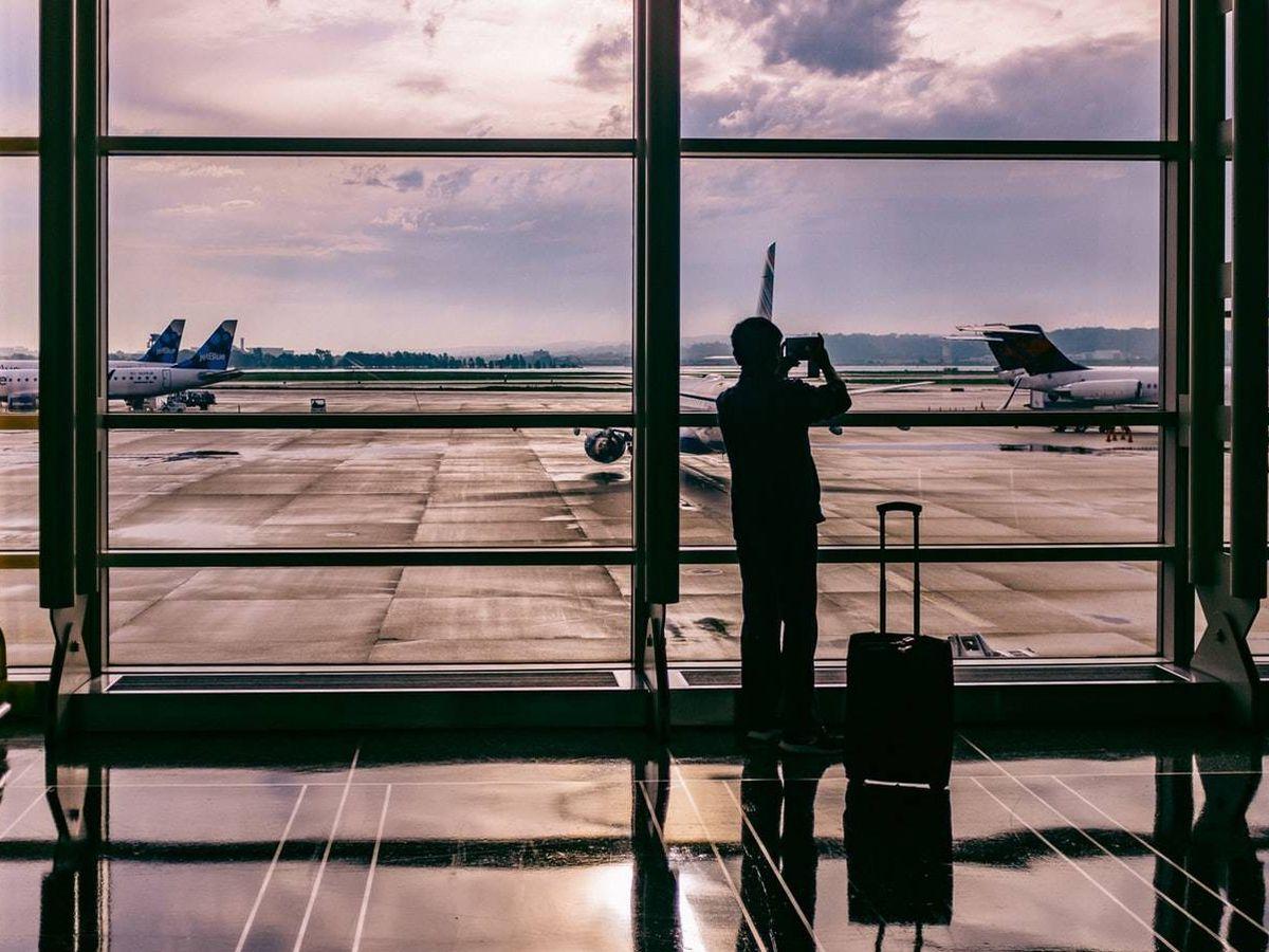 Foto: Un hombre junto a su equipaje de mano espera en un aeropuerto. (Foto: Unsplash)
